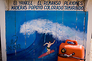 A mural on the side of a shop stand advertises boat trips to the main surf breaks and beaches in San Juan Del Sur, Nicaragua. Locals have found a market by catering to tourists who want to beaches that are difficult or inaccessible by road. San Juan Del Sur used to be an unknown treasure for surfers, but has seen an increase of tourists with the popularization of Nicaragua's waves.