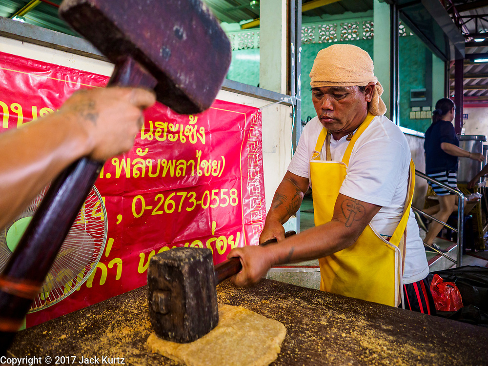 20 OCTOBER 2017 - BANGKOK, THAILAND: Men using wooden mallets to make Chinese peanut brittle at Chao Zhou Shi Kong Shrine in Bangkok's Chinatown on the first day of the Vegetarian Festival, what Thais call the Taoist Nine Emperor Gods Festival, in the Chinatown neighborhood of Bangkok, Thailand. It is a nine-day Taoist celebration beginning on the eve of 9th lunar month of the Chinese calendar. For nine days people participating in the festival wear only white and don't eat meat, poultry, seafood, and dairy products. The vegetarian festival is celebrated throughout Thailand, but especially in Phuket and Bangkok, cities with large ethnic Chinese communities.       PHOTO BY JACK KURTZ