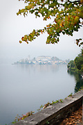 The island of Isola San Giulio on a foggy afternoon on Lake Orta, Piedmont, Italy.