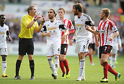 Swansea City's Michu and Sunderland's Sebastian Larsson confront the ref after a challenge outside the box.- Photo mandatory by-line: Alex James/JMP - Tel: Mobile: 07966 386802 19/10/2013 - SPORT - FOOTBALL - Liberty Stadium - Swansea - Swansea City v Sunderland - Barclays Premier League