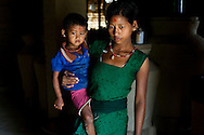 Pramila Tharu, 15, carries her 2 year old toddler Prapti, in Bhaishahi village, Bardia, Western Nepal, on 29th June 2012. Pramila eloped and married at 12 and gave birth to Prapti at age 13. She delivered prematurely on the way to the hospital in an ox cart and her baby weighed only 1.5kg at birth. In Bardia, StC works with the district health office to build the capacity of female community health workers who are on the frontline of health service provision like ante-natal and post-natal care, especially in rural areas. Photo by Suzanne Lee for Save The Children UK