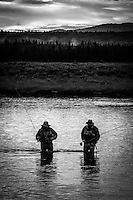 Two fly fisherman wade through the Henry's Fork River in Idaho on their way back to the car after a evening fishing to rising trout.