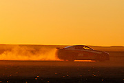 epa03878321 A modified Twin Turbo Nissan 370Z is driven across the desert at sunset during the 2013 Kalahari Desert Speedweek at Hakskeenpan, Northern Cape of South Africa, 21 September 2013. The Speedweek sees motorsport enthusiasts gathering in a remote desert in the north of the country to drive their vehicles across seven kilometers of specially prepared clay track for high speed top end runs. Technically the desert Speedweek is more challenging than Tar Speedweek and requires much more driving and engineering skills for top honours in each class including cars and bikes.  EPA/NIC BOTHMA