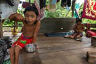 Niña comiendo y Mujer Embera en su choza tejiendo una cesta tradicional.  Comunidad indígena La Chunga, Comarca Embera – Wounaan en la Provincia de Darién, Panamá.  La Chuga, ubicada en el  Rio Sambu, forma parte del corredor biológico de Bagres con sus inmensos bosques tropicales.
