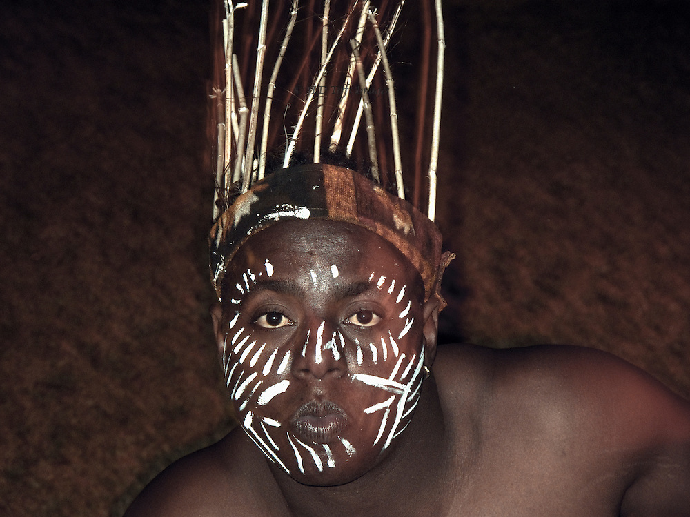 Head of a Sidi man, descended from African immigrants to Gujarat, during a dance performance.  He wears a coronet of sticks and his dark face is covered with painted white stripes.
