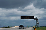 A lone vehicle passes a hurricane warning sign under storm clouds as it heads south approaching Victoria, Texas August 25, 2017. REUTERS/Rick Wilking