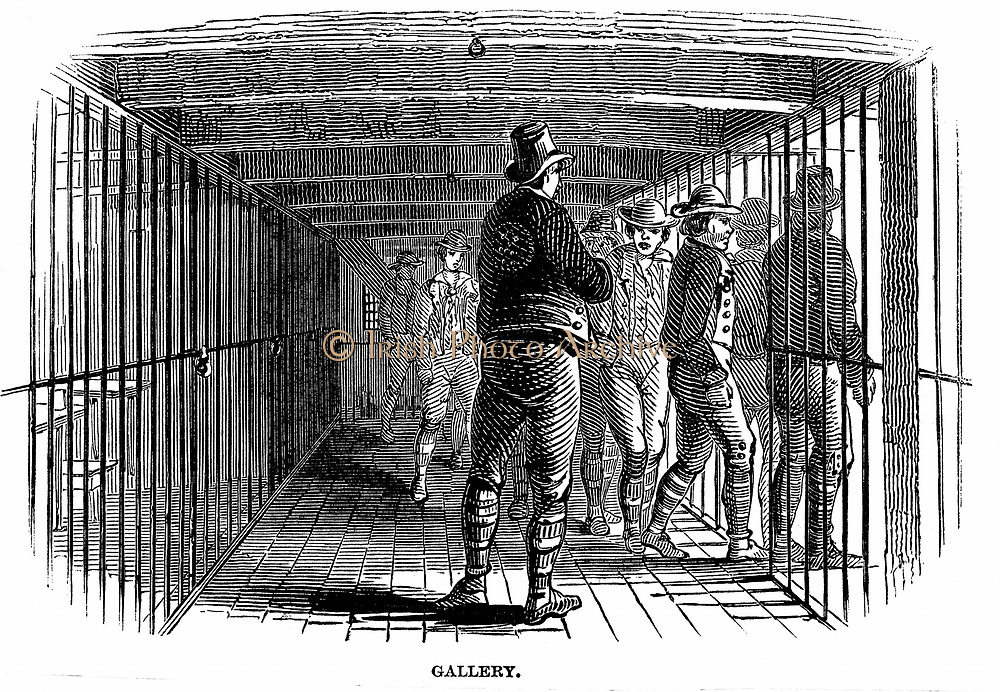 Prison Hulks: Warder watching prisoners entering their ward on board convict hulk 'Warrior' at Woolwich. This hulk held 600 and was an intermediate confinement between an ordinary gaol or transportation.  Prisoners were used as labourers in the navy dockyards. The Hulks (Tenders) were usually naval vessels that were no longer seaworthy.  From 'The Illustrated London News', 1848. Wood engraving.