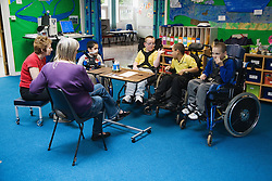 Group of children with physical disabilities in a class discussion,