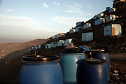 Plastic containers stand aside shackhouses waiting for water on pipe trucks at the human settlement of Defensores de la Familia, early Monday, April 17, 2011. (Dado Galdieri)