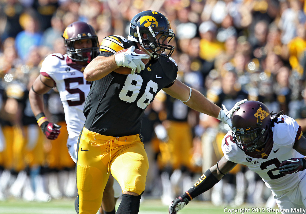 September 29 2012: Iowa Hawkeyes tight end C.J. Fiedorowicz (86) stiff arms Minnesota Golden Gophers defensive back Troy Stoudermire (2) after a catch during the first quarter of the NCAA football game between the Minnesota Golden Gophers and the Iowa Hawkeyes at Kinnick Stadium in Iowa City, Iowa on Saturday September 29, 2012. Iowa defeated Minnesota 31-13 to claim the Floyd of Rosedale Trophy.