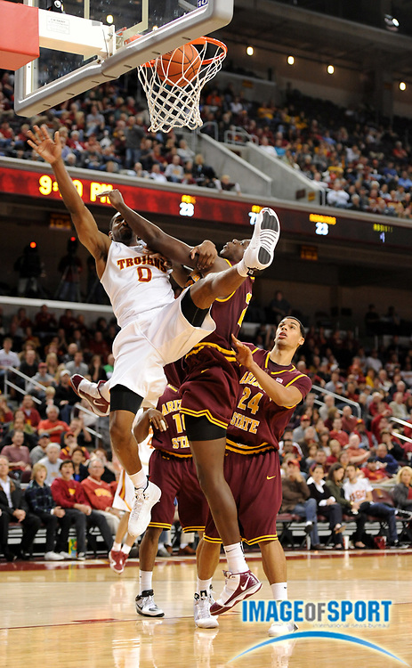 Jan 2, 2010; Los Angeles, CA, USA; Southern California Trojans forward Marcus Johnson (0) is fouled by Arizona State Sun Devils center Eric Boateng (2) at the Galen Center. USC defeated Arizona State 47-37.