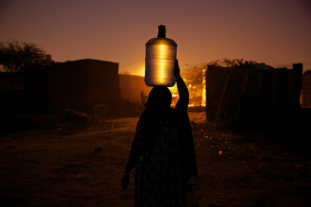 Silhouette of a woman carrying water bottle on head, India