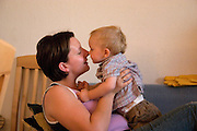 Pregnant mom and son taking a moment to rub noses while relaxing at home. Balucki District Lodz Central Poland