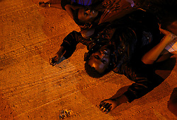 An exhausted would-be immigrant lies on the ground after disembarking from a Armed Forces of Malta (AFM) patrol boat at the AFM Maritime Squadron base at Haywharf in Valletta's Marsamxett Harbour early July 10, 2013. Sixty-eighty African immigrants were rescued by the AFM, 70 nautical miles south of Malta from a vessel in distress while trying to reach European soil from Africa, according to army sources. REUTERS/Darrin Zammit Lupi (MALTA - Tags: HEALTH SOCIETY IMMIGRATION POLITICS) MALTA OUT. NO COMMERCIAL OR EDITORIAL SALES IN MALTA - RTX11IXE