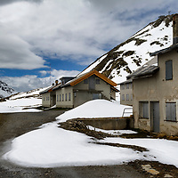 Buildings close to the summit of the Furka Pass (2431m) connecting Uri and Valais. Photographed shortly before the road closed for a seven month winter. Historically this area, around Uri belonged to teh National Redoubt, the final Swiss line of defence in the high alps, and is checked with the remains of millitray installations, many of them underground, still camouflaged.