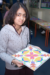 Young girl showing a piece of Rangoli art at Diwali; Festival of Light,