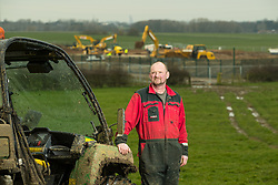 © Licensed to London News Pictures . 10/03/2017 . Preston , UK . Farmer Allan Wensley at Plumpton Hall Farm , with the Cuadrilla fracking site behind . Allan faces protests from neighbours and environmental campaigners after renting fields around his farm to fracking firm Cuadrilla . Photo credit : Joel Goodman/LNP