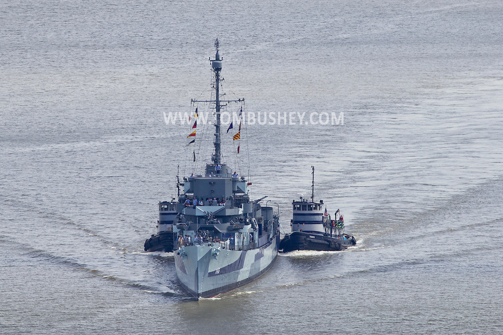 Highland, New York - The USS Slater makes its way north on the Hudson River on June 30, 2014. The Slater served in World War II and is the last destroyer escort vessel afloat in America. The Slater was on the way to Albany, N.Y., to resume its duties as a floating museum. The tugboats Frances, right, and Margot, assisted the Slater.