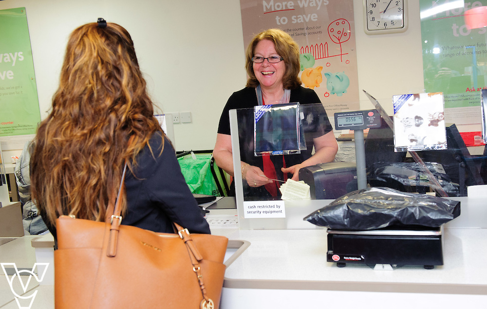 Pictured is Jane Sharpe serving customer Lauren Brown<br /> <br /> Jane Sharpe, who works at Peterborough Post Office, has been nominated as a One Hero by her colleague Adeel Shabir.  <br /> <br /> Date: February 4, 2016