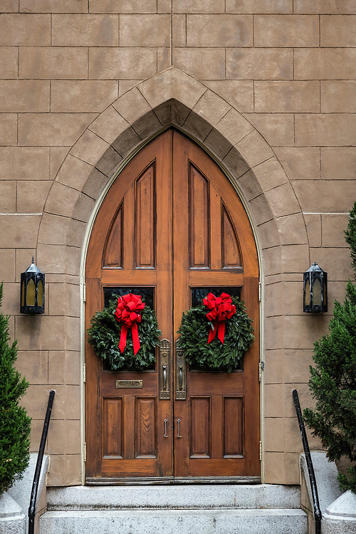 Christmas wreaths on charming church door.