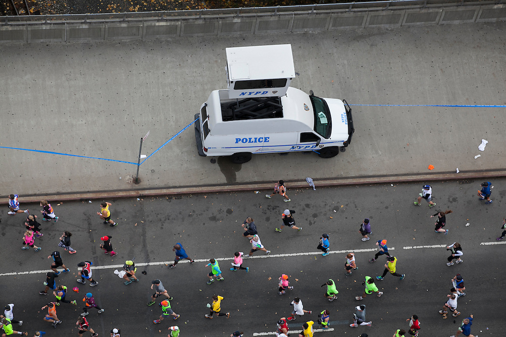 A NYPD van is set up on the sidewalk as participants run in the New York City Marathon on 4th Ave in Brooklyn, NY on Sunday, Nov. 3, 2013.<br /> <br /> CREDIT: Andrew Hinderaker for The Wall Street Journal<br /> SLUG: NYSTANDALONE