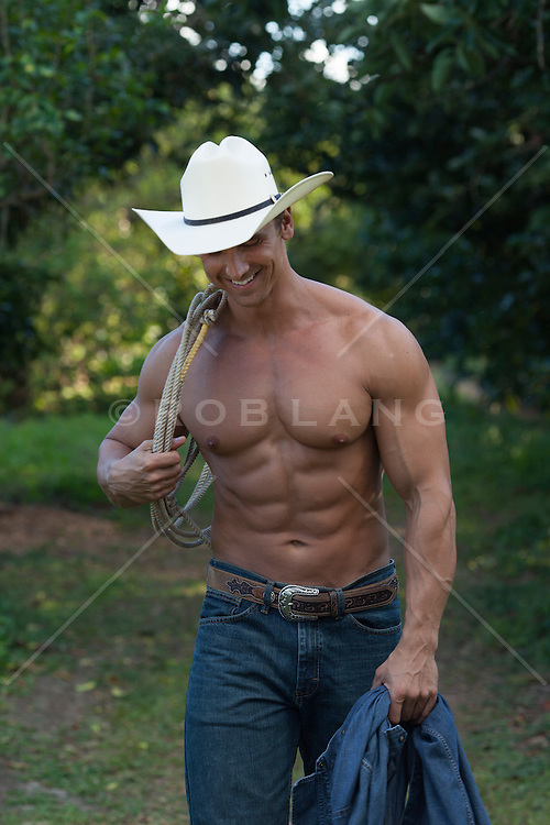 masculine muscular cowboy without a shirt walking in a field smiling and carrying a lasso