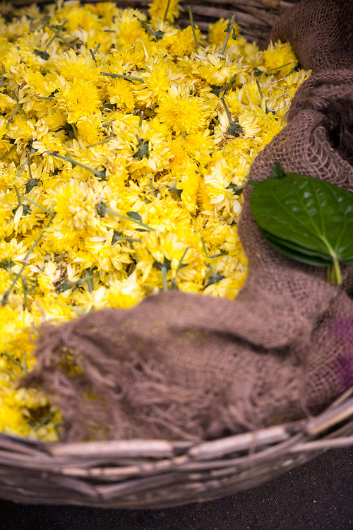 PUTTARPATHI, INDIA - 27th October 2019 - Close-up of a basket of yellow flowers for sale at a market in Puttarpathi, Andhra Pradesh, South India