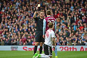 Aston Villa midfielder Gary Gardner (22) is shown a yellow card for a tackle on Fulham midfielder Stefan Johansen (14) during the EFL Sky Bet Championship match between Fulham and Aston Villa at Craven Cottage, London, England on 17 April 2017. Photo by Jon Bromley.