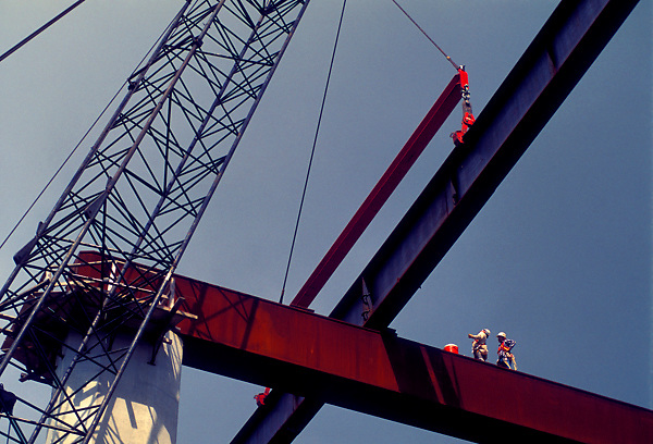 Stock photo of a beam being brought into position by a heavy crane as workmen observe.