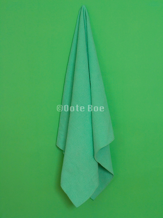 green towel hanging against a green wall