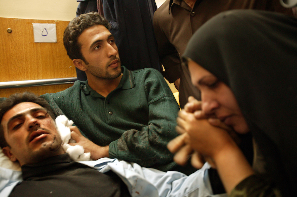 Policeman Amir Abdul Khadar, 29, is comforted by relatives at the local hospital, Iskandariyah, Iraq, Feb. 10, 2004. Khaled sustained injuries when a truck packed with an estimated 500 pounds of explosives blew up at a police station. Dozens of would-be recruits were lined up to apply for jobs at the station. A hospital official said at least 50 people were killed and 50 others wounded. The local Iraqi police commander, Lt. Col. Abdul Rahim Saleh, said the attack was a suicide operation, carried out by a driver who detonated a red pickup as it passed the station.