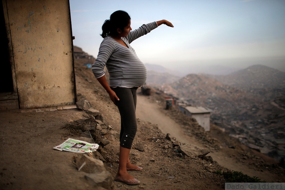 Lorena, a 21 old girl from Cajamarca is about to give birth to a boy but she doesn't mention wether the father is going to recognize fatherhood or not. She outlooks the hundreds of shanty houses balancing at the top of sand dunes in Pamplona Alta neighborhood  in the outskirts of the Peruvian capital, Wednesday, March 13, 2011. The 21st century Lima presents an unstoppable growing, with an evident increment on its marginal population. This uncontrolled migration from the countryside to the capital is the unwanted effect from a combination of several factors: the civil war that stroke the country's rural areas during the 80's expelling the first settlers, a decade of sustained economic growth after the violent end of the conflict,  years of political forgiveness of the Amazon and Andean areas; a cultural, political and economical centralism and the sloppy, corrupted management of public resources.  Despite its enormous water vulnerability and limitations - having been built over the sand dunes reaching the Pacific Ocean, being influenced by a rainless weather pattern and relying in the water supply from melting Andean glaciers - Lima still lures and moves thousands of farmers and people from the countryside in search of better education and jobs at the desert city. The survival challenges for this huge human settlement of 8 million souls are defined by its water resources. Its growing and living standard defined by the absence of it. The colonization of the area , a historic mistake never committed by the Inca empire, but which the Spaniards prefer to ignore in their search for wealth is the curse of a growing population and retreating water supply.   (Photo Dado Galdieri)