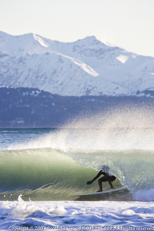 Alaskan surfer Tim Bowler gets in the tube, or barrelled, during a cold winter surf session in Homer, Alaska. The snowy Kenai mountain range rises from Kachemak Bay in the background.