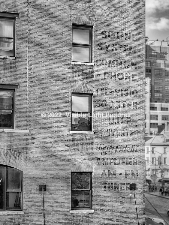 Worn painted advertisement for audio video systems on the side of a brick building in the meat-packing district of New York City in Manhattan