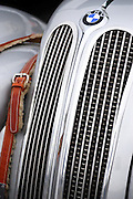Detail of the front grill of a vintage classic BMW automobile.  Shearling leather straps and gleaming chrome reference the style of utility of a bygone era.<br /> <br /> Seen at Laguna Seca during the Historic racing events of Monterey Car Week