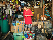 04 JANUARY 2016 - BANGKOK, THAILAND:          A woman shops for housewares in a small stand in Bang Chak Market on the last day the market was open. The market closed January 4, 2016. The Bang Chak Market serves the community around Sois 91-97 on Sukhumvit Road in the Bangkok suburbs. About half of the market has been torn down. Bangkok city authorities put up notices in late November that the market would be closed by January 1, 2016 and redevelopment would start shortly after that. Market vendors said condominiums are being built on the land.       PHOTO BY JACK KURTZ
