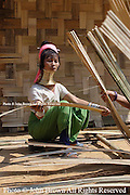 Karen Paduang refugees from Burma (Myanmar) construct a roof for their home in Ban Nai Soi, Thailand. The Karen people fled Burma to escape from war atrocities and are considered a tourist attraction by the Thai government.