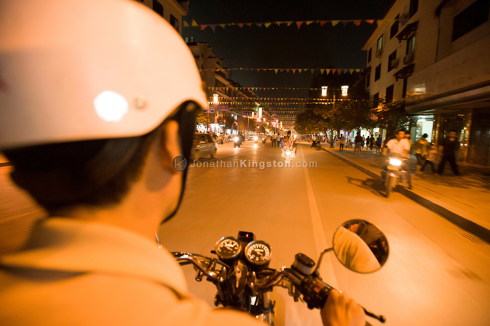 Point of view image of a man riding a motorcycle at night on a street in Yangshuo, China.