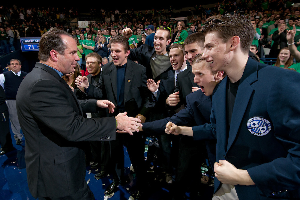 Head coach Mike Brey greets members of the Leprechaun Legion after Notre Dame defeated the West Virginia Mountaineers 71-44 at the Purcell Pavilion.