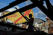 A man salvages wood from a wrecked house frame to use in the reconstruction of his own house.