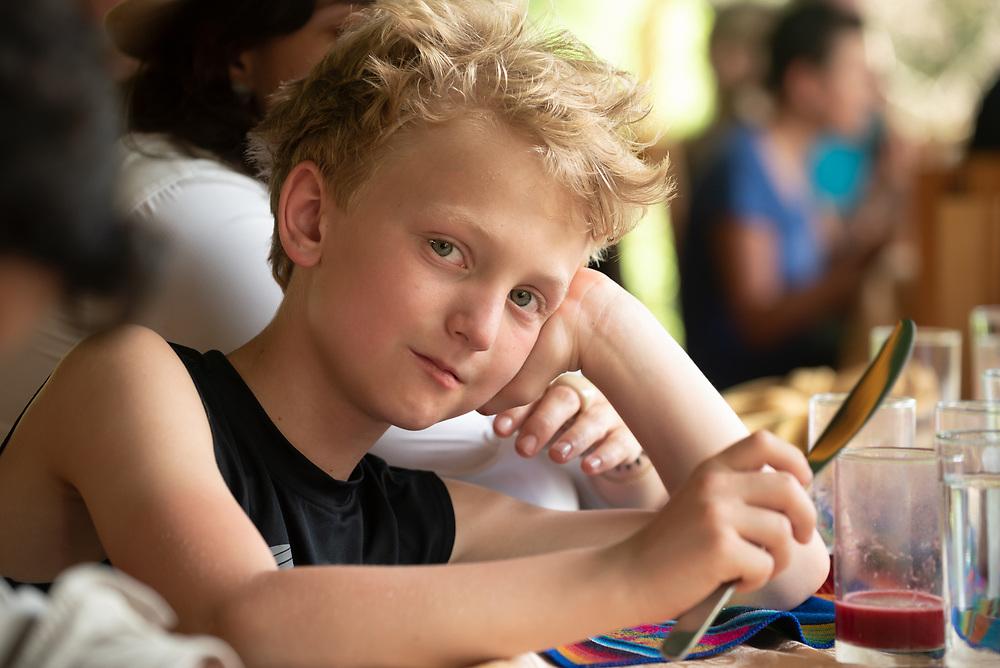 Boy holding a butter knife at a restaurant.