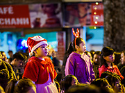 22 DECEMBER 2017 - HANOI, VIETNAM: A woman with her children, wearing Santa Claus hats, during the Christmas show at St. Joseph's Cathedral in Hanoi. There are about 5.6 million Catholics in Vietnam. The Cathedral was one of the first structures built by the French during the colonial era and was opened in 1886. It's one of the most popular tourist attractions in Hanoi.    PHOTO BY JACK KURTZ