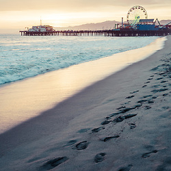 Santa Monica Pier sunset retro vertical photo with footprints in the sand along the Pacific Ocean. Santa Monica is a coastal beach city in Southern California in the United States. Copyright ⓒ 2017 Paul Velgos with All Rights Reserved.