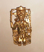 Gold pendant depicting a ruler with ritual regalia AD1200-1521.  This ruler, richly adorned with headdress necklace and earrings, bears a serpent staff battleaxe in his right hand and a shield in his left.  From his hip plug hangs a mask, possibly an ancestral relic. Aztec