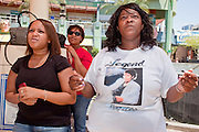 Jul 7, 2009 -- GLENDALE, AZ: DEON TILLMAN, left, WANDA PREYER and her daughter JENNIFER PREYER watch the memorial service for Michael Jackson in Glendale, AZ. About 35 people came to Westgate Center, a shopping and dining complex in Glendale, a suburb of Phoenix, AZ, to watch the memorial service for Michael Jackson. The service was simulcast live from the Staples Center in Los Angeles on jumbotrons around the complex. Photo by Jack Kurtz