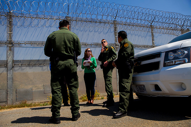 U.S. Customs and Border Patrol Deputy Chief Patrol Agent Rodney Scott talks to Lisa Halverstadt between two border fences.