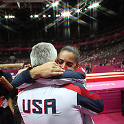 Alexandra Raisman, USA,  reacts as she hugs her coach Mihai Brestyan after her position upgraded from fourth to third during the Women's Gymnastics Apparatus Beam final at North Greenwich Arena during the London 2012 Olympic games London, UK. 7th August 2012. Photo Tim Clayton