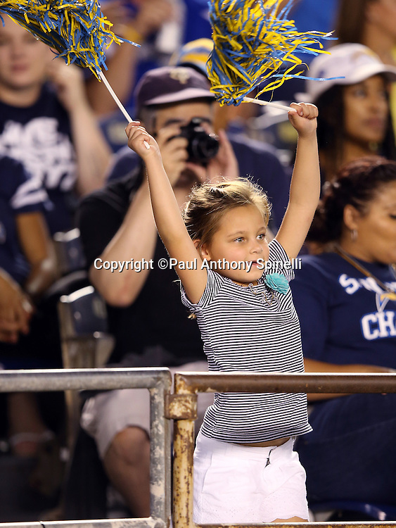 A young San Diego Chargers fan cheers and waves pom poms during the 2015 NFL preseason football game against the Dallas Cowboys on Thursday, Aug. 13, 2015 in San Diego. The Chargers won the game 17-7. (©Paul Anthony Spinelli)