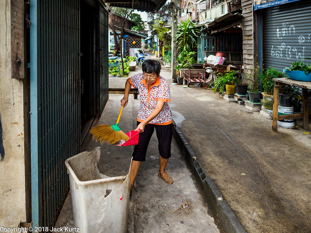 "22 MARCH 2018 - BANGKOK, THAILAND: One of the remaining shop owners along Khlong Lat Phrao sweeps up the front of her shop. Bangkok officials are evicting about 1,000 families who have set up homes along Khlong  Lat Phrao in Bangkok, the city says they are ""encroaching"" on the khlong. Although some of the families have been living along the khlong (Thai for ""canal"") for generations, they don't have title to the property, and the city considers them squatters. The city says the residents are being evicted so the city can build new embankments to control flooding. Most of the residents have agreed to leave, but negotiations over compensation are continuing for residents who can't afford to move.       PHOTO BY JACK KURTZ"