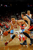 Wolfpack guard Devon Daniels (24) drives around a UVA defender during ACC action in PNC Arena.